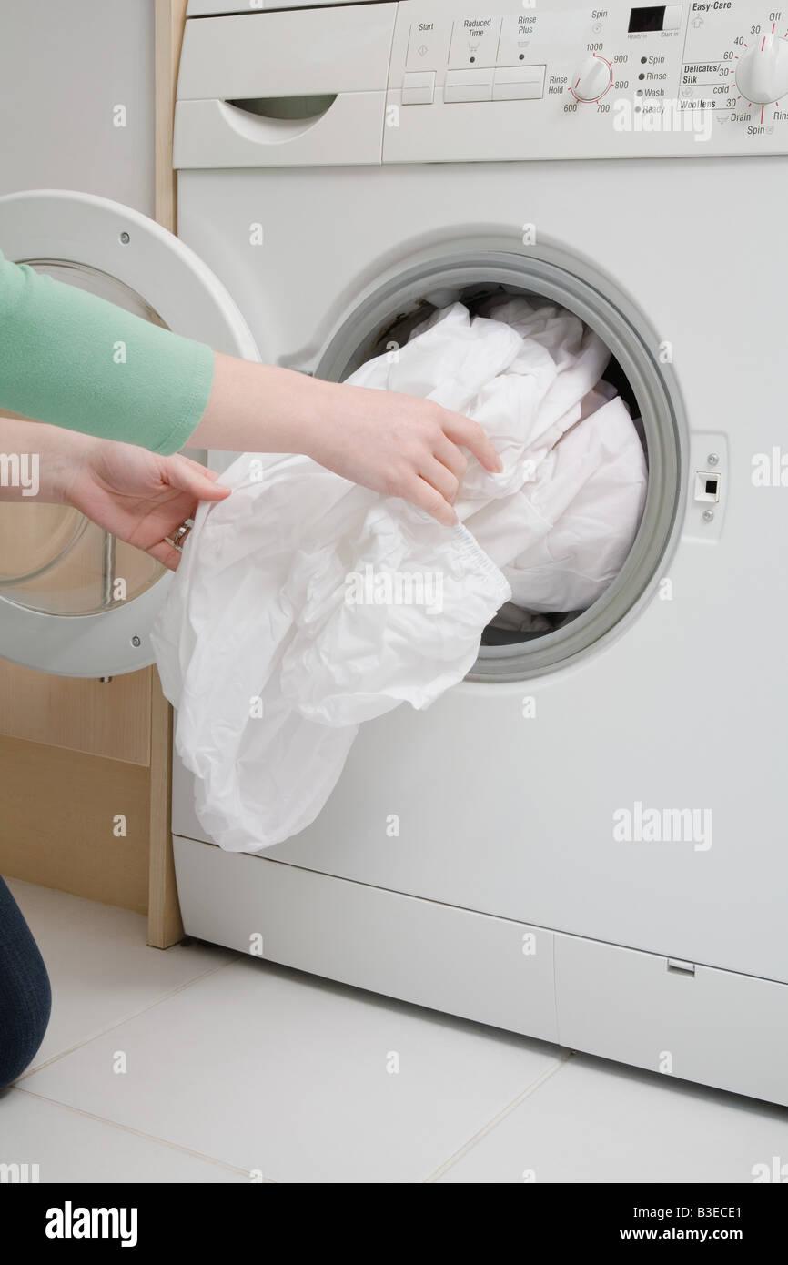 Woman taking sheet from washing machine - Stock Image