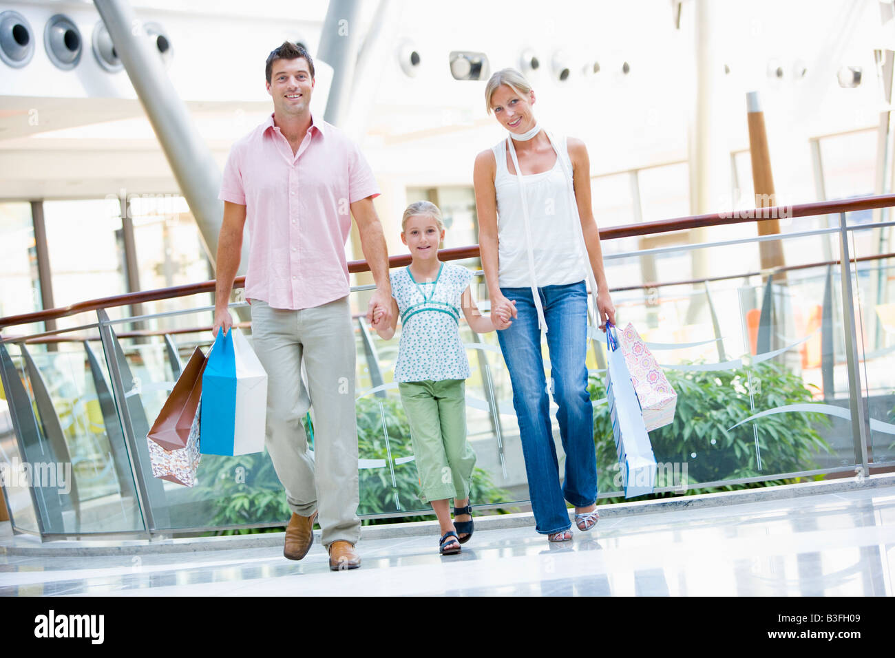 Mother and father with young daughter at a shopping mall - Stock Image