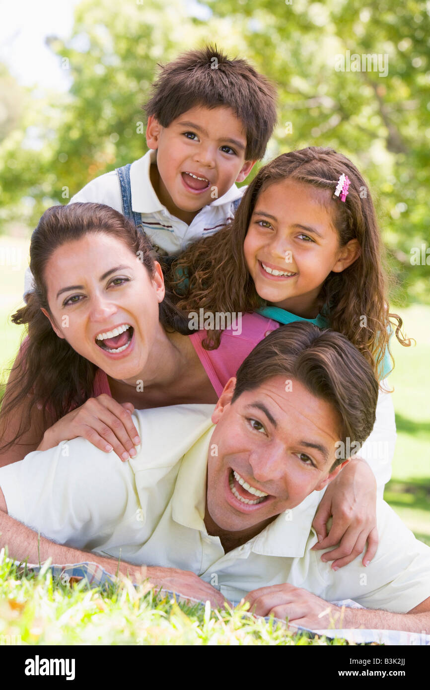 Family lying outdoors smiling - Stock Image