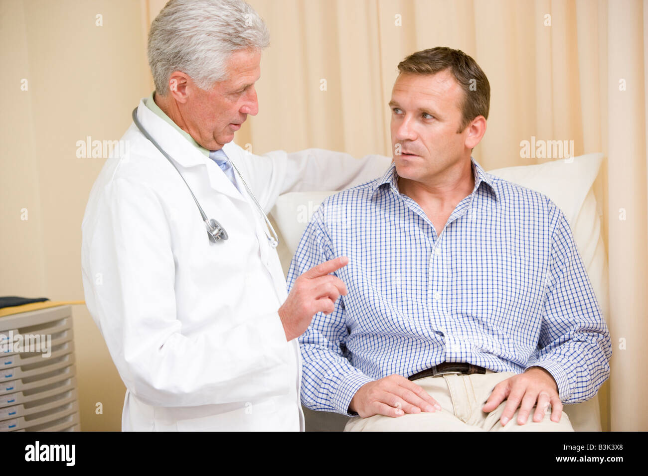Doctor giving man checkup in exam room Stock Photo
