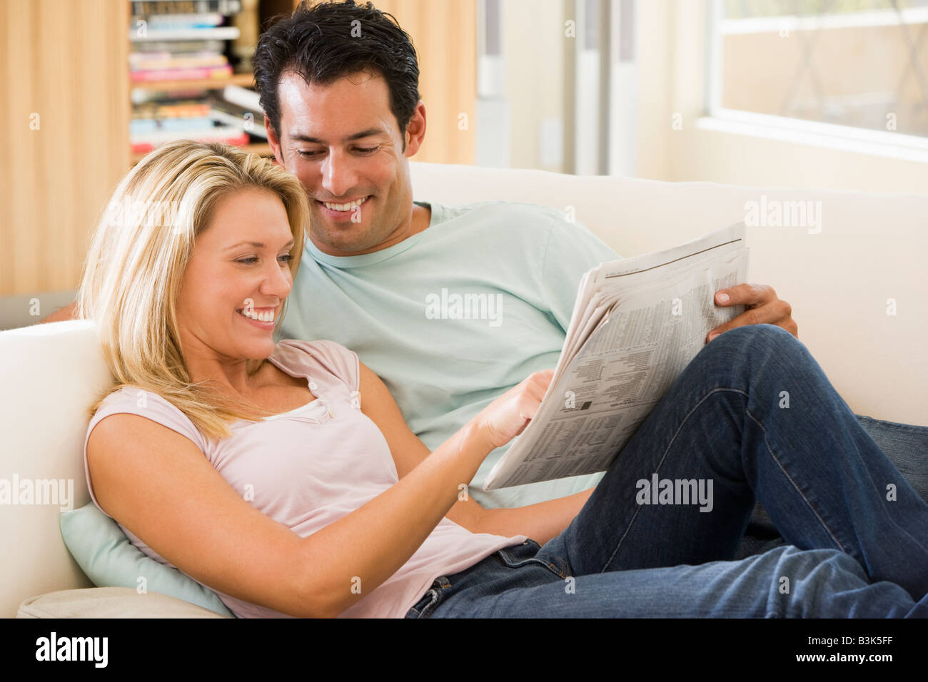 Couple in living room reading newspaper and smiling - Stock Image