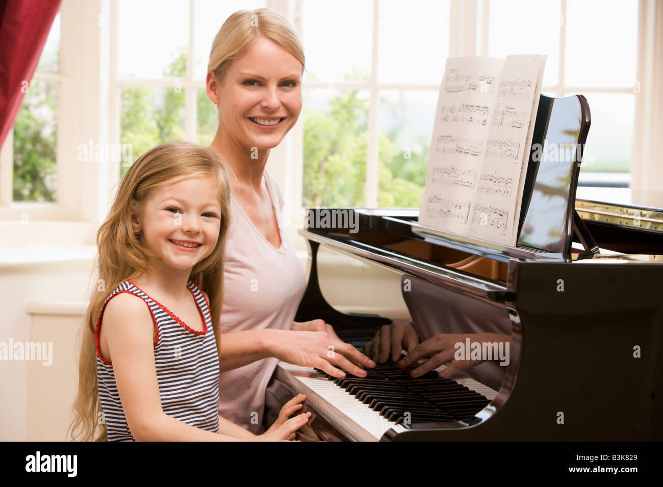 Woman and young girl playing piano and smiling - Stock Image