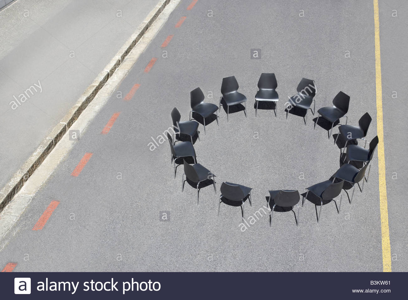 Circle of office chairs in roadway - Stock Image