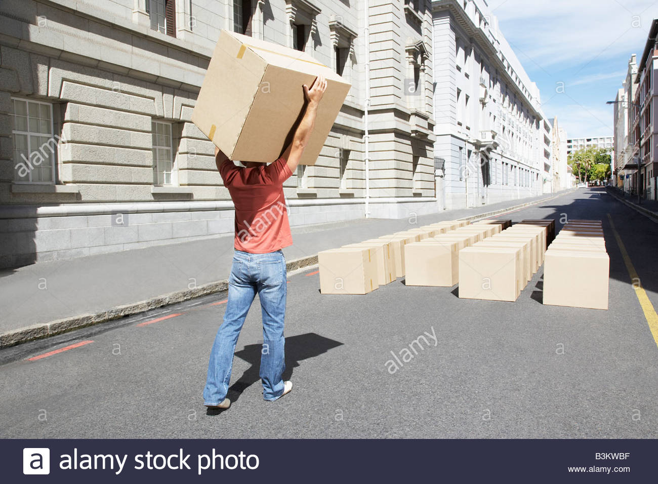 Man carrying box in roadway - Stock Image