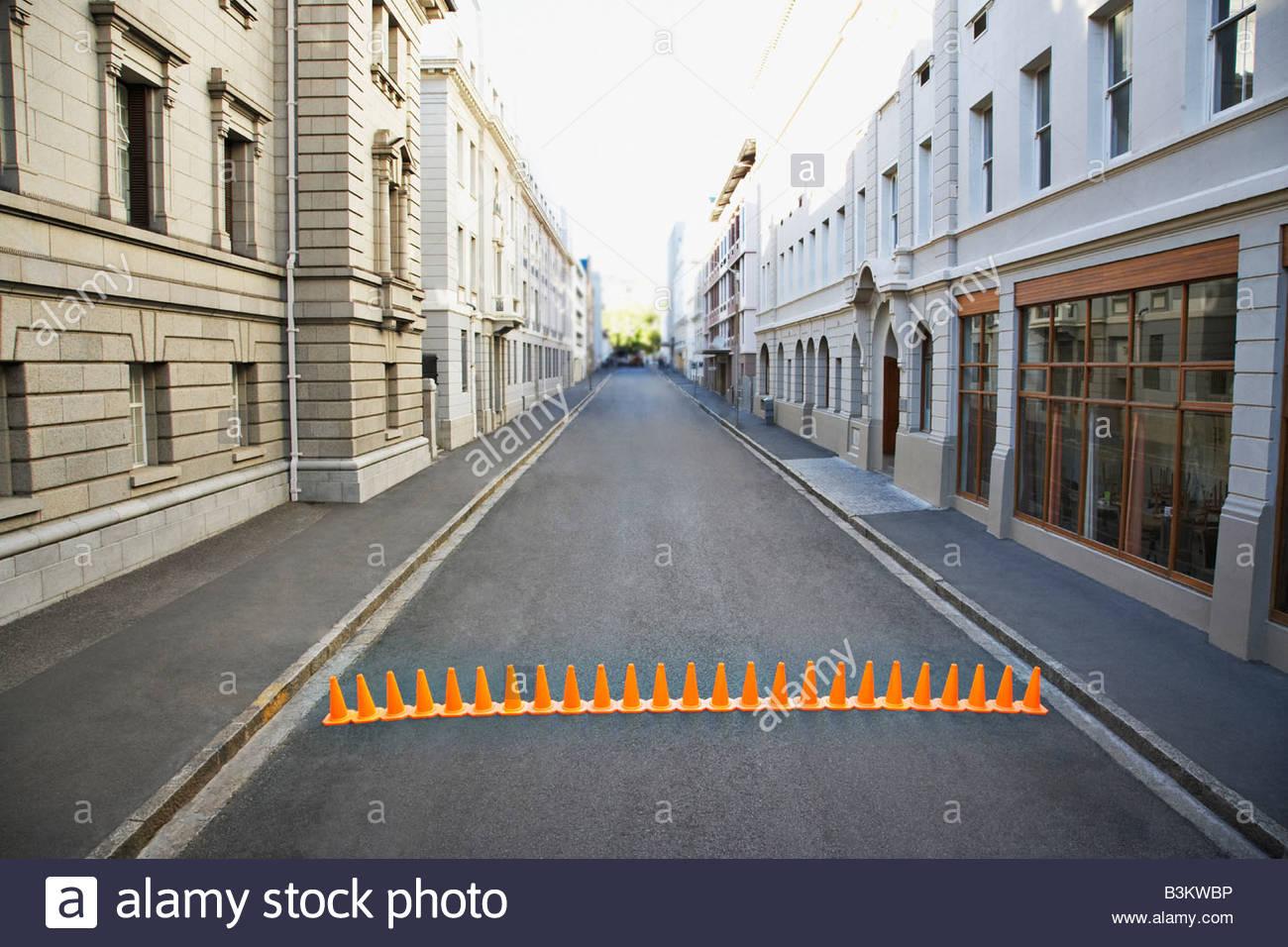 Line of traffic cones in urban roadway - Stock Image
