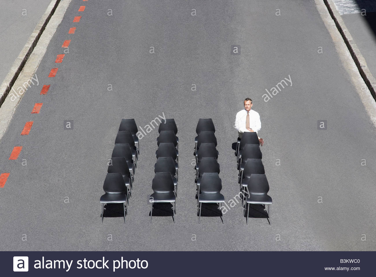 Businessman sitting in office chairs in roadway - Stock Image
