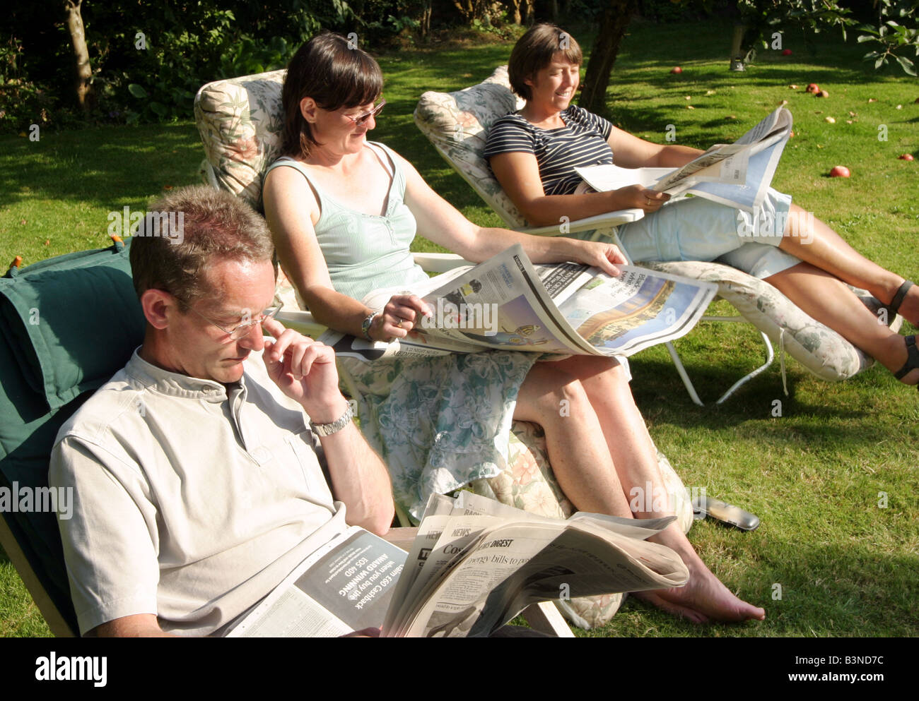 three-adults-reading-the-saturday-papers-in-the-garden-newmarket-suffolk-B3ND7C.jpg
