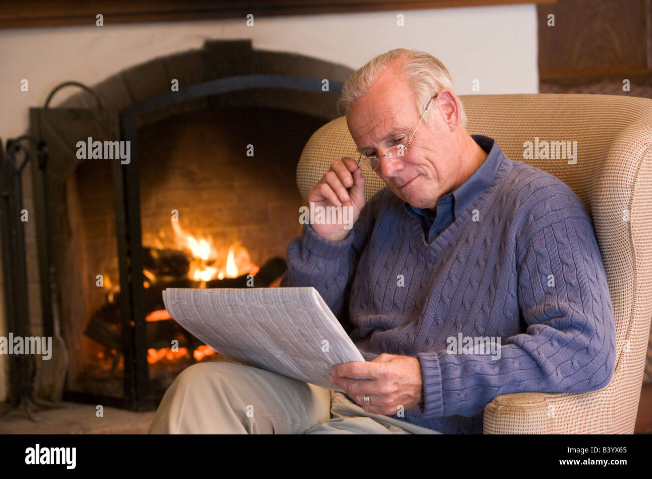 Man sitting in living room by fireplace with newspaper - Stock Image