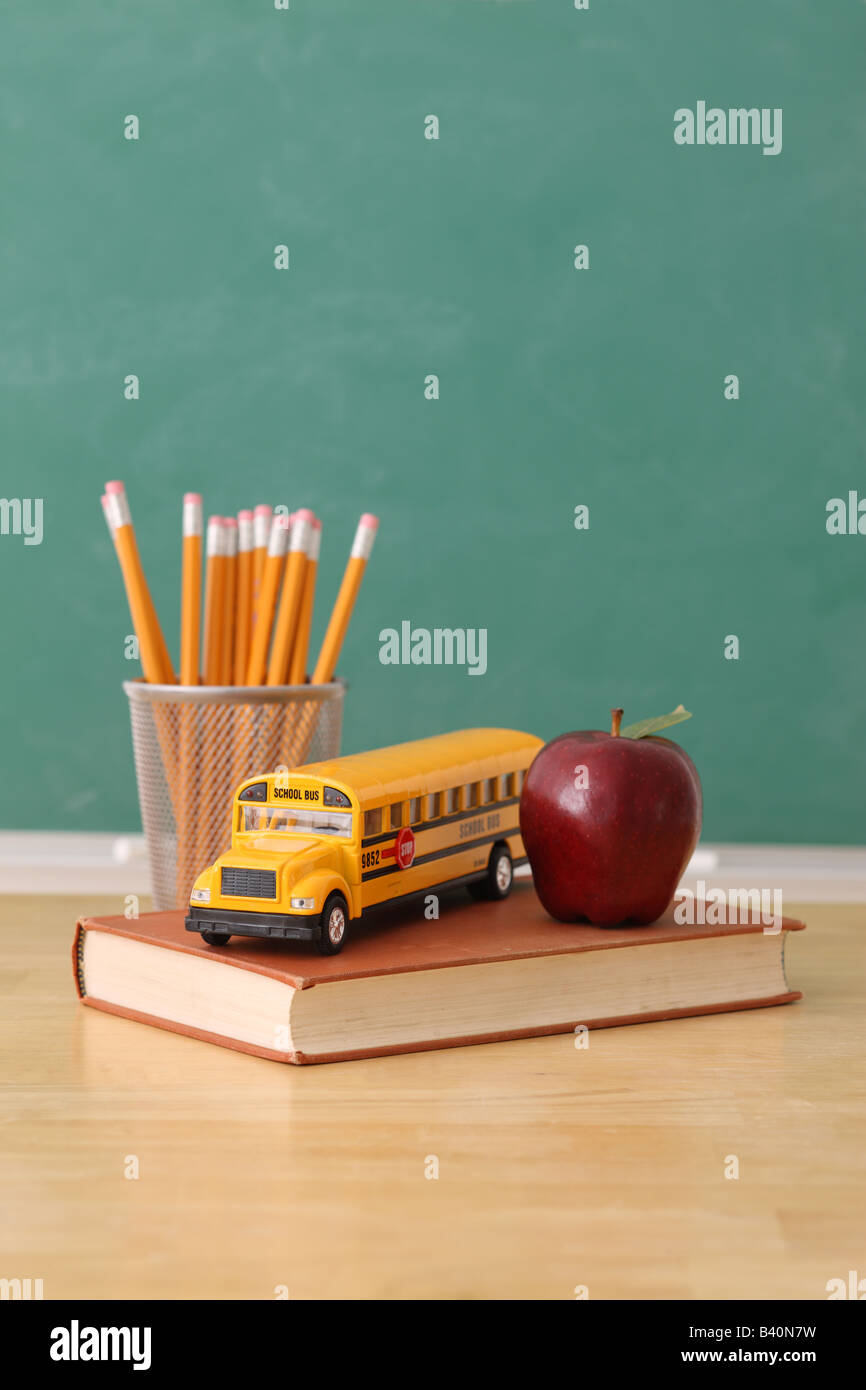 School education still life with pencils apple book and toy school bus chalkboard background - Stock Image