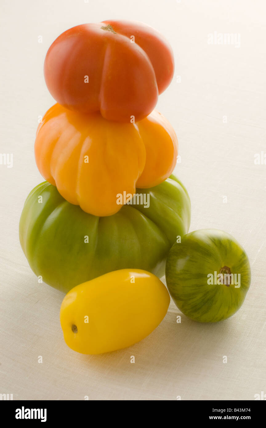 A stack of five ripe red orange gold yellow and green heirloom tomatoes Stock Photo