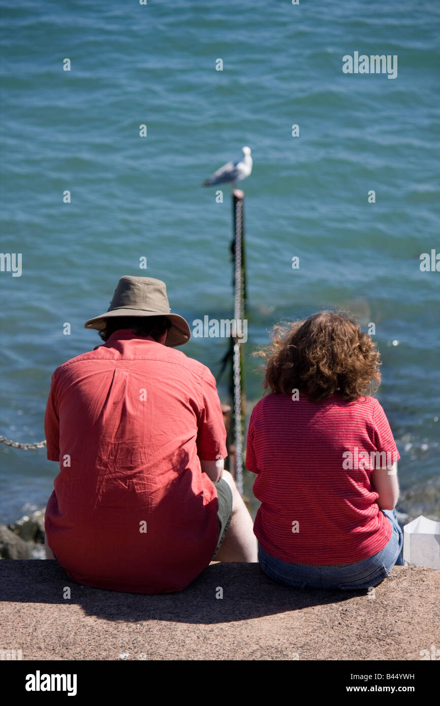 couple-sitting-beside-the-sea-lyme-regis-dorset-B44YWH.jpg