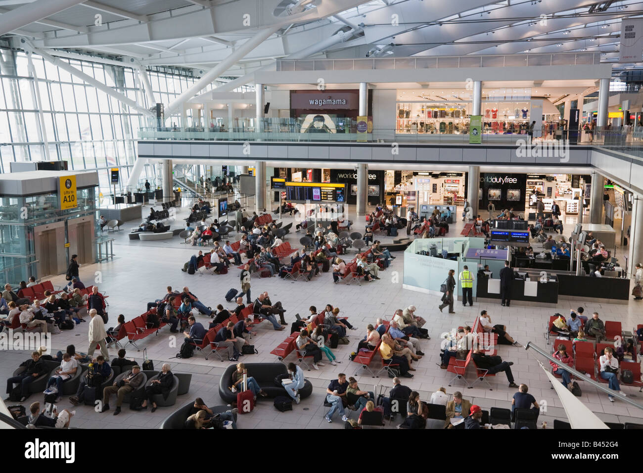 People in London Heathrow Airport British Airways departures lounge inside Terminal 5 building with duty free shops - Stock Image