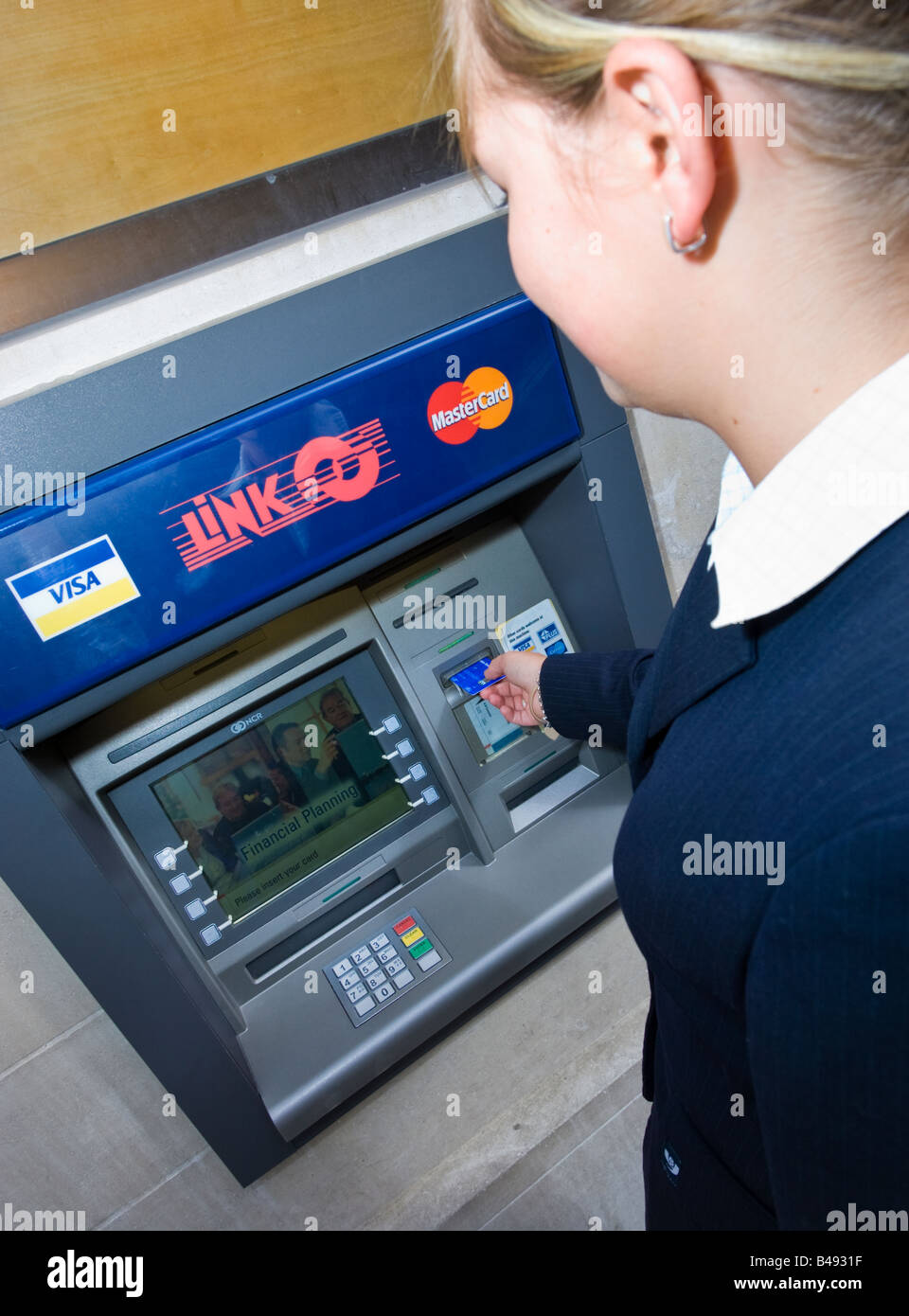 Young businesswoman in suit inserting card into a Link cash point machine ATM UK Stock Photo
