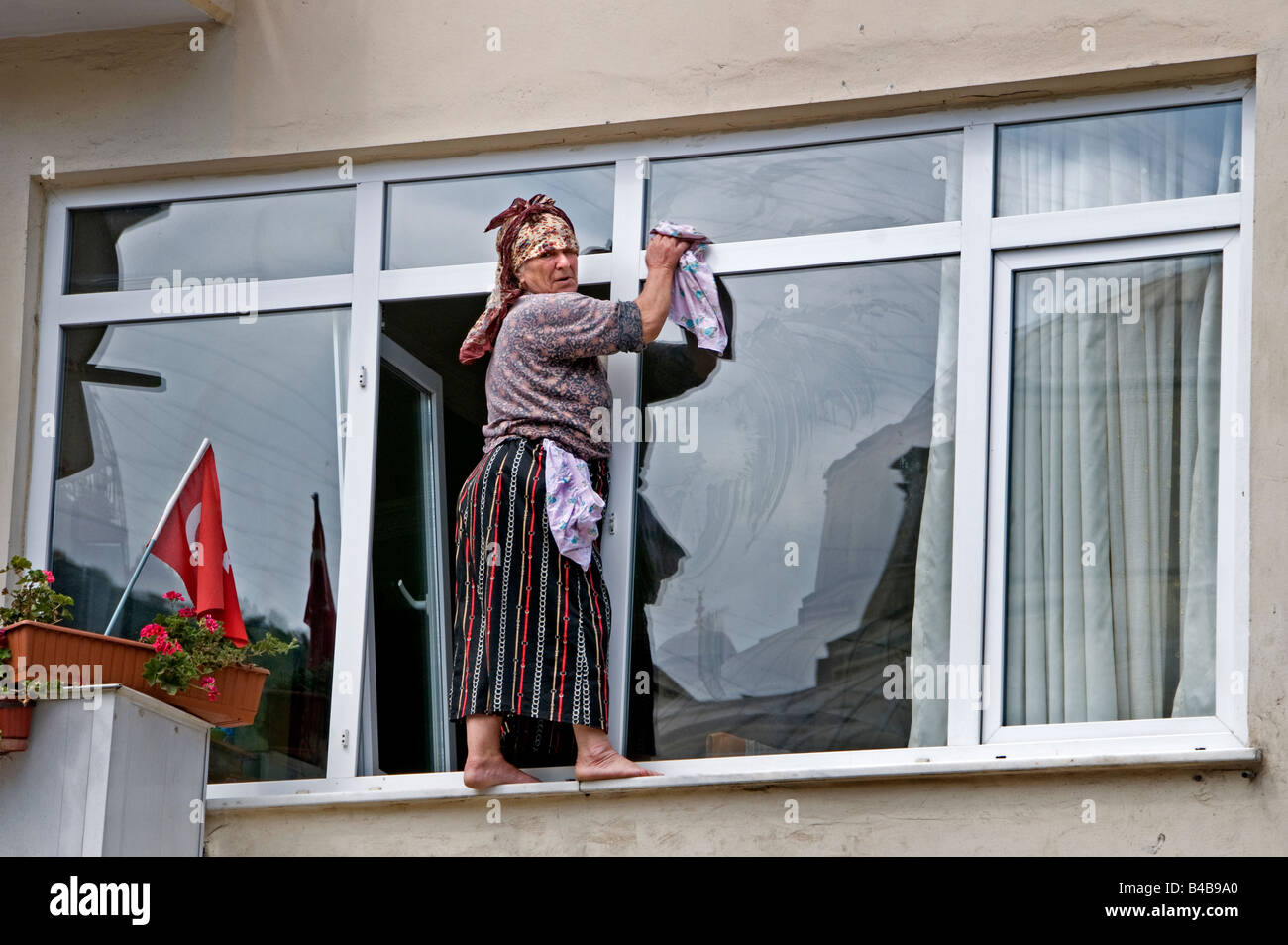 Istinye cleaning woman window windows cleaners dangerous, perilous, risky, hazardous - Stock Image