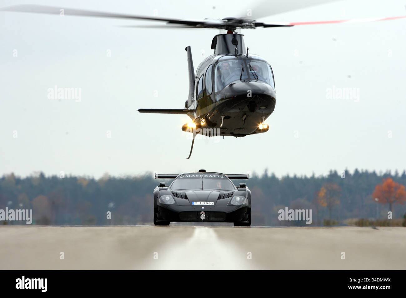 Maserati MC 12 Corsa, model year 2007-, black, driving, frontal view, Airport, Helicopter - Stock Image