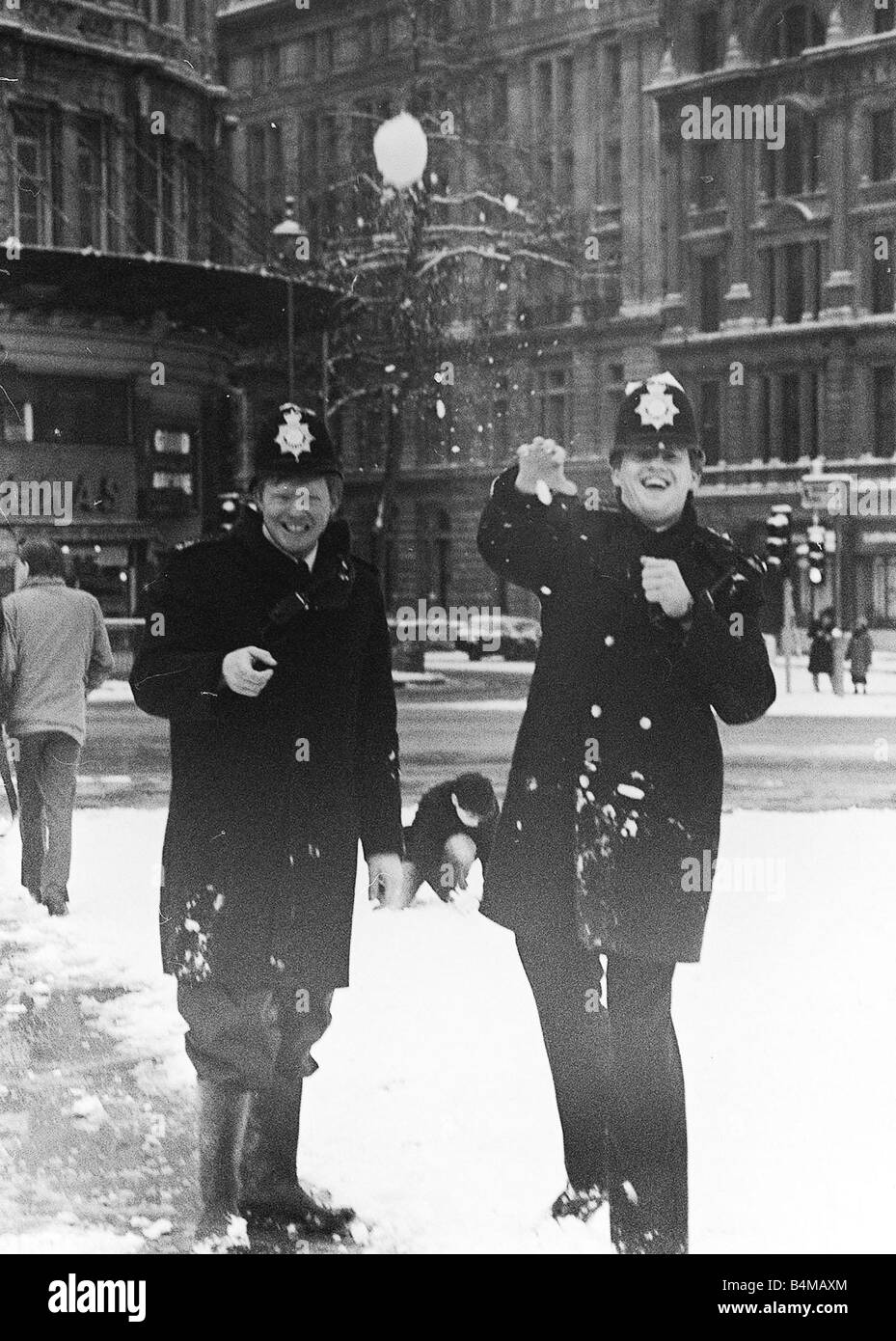Policemen having a snow ball fight in London after a heavy snow fall January 1985 Stock Photo