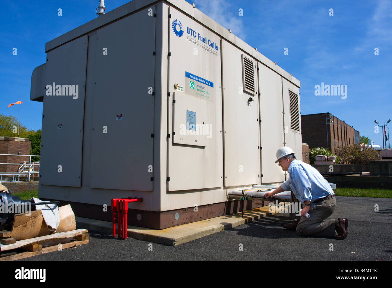 An engineer looks over a fuel cell power generator in Connecticut USA - Stock Image