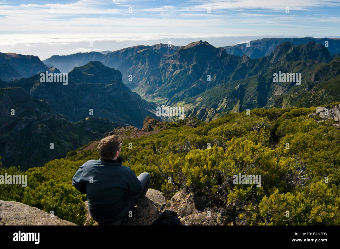 Walker surveys the view from Pico Ruivo Madeira s highest summit with Curral das Freiras far below - Stock Image