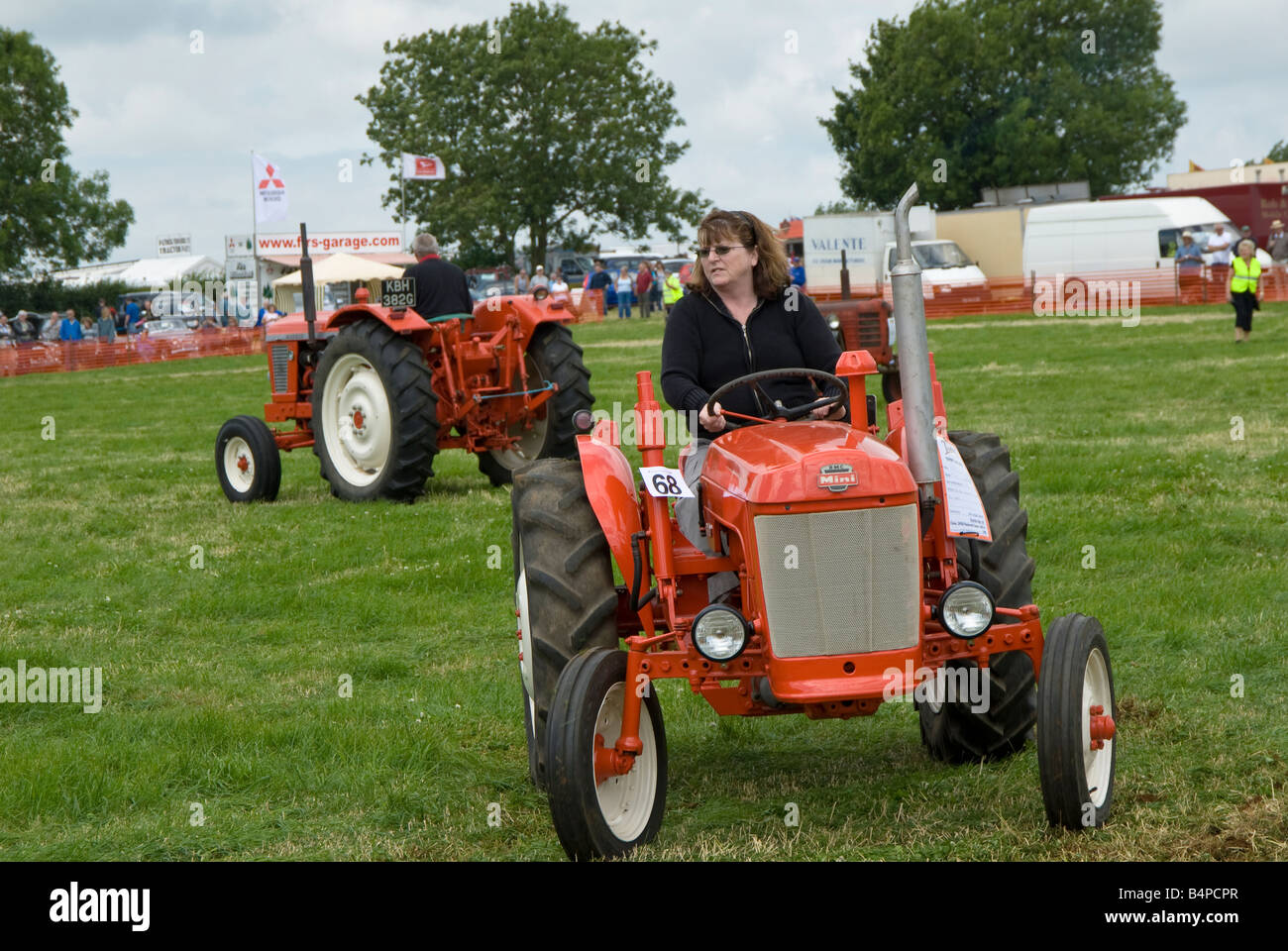 A lady enthsiast drives her BMC Mini Tractor around the parade ring at Bloxham Vintage Vehicle and Country Show. - Stock Image