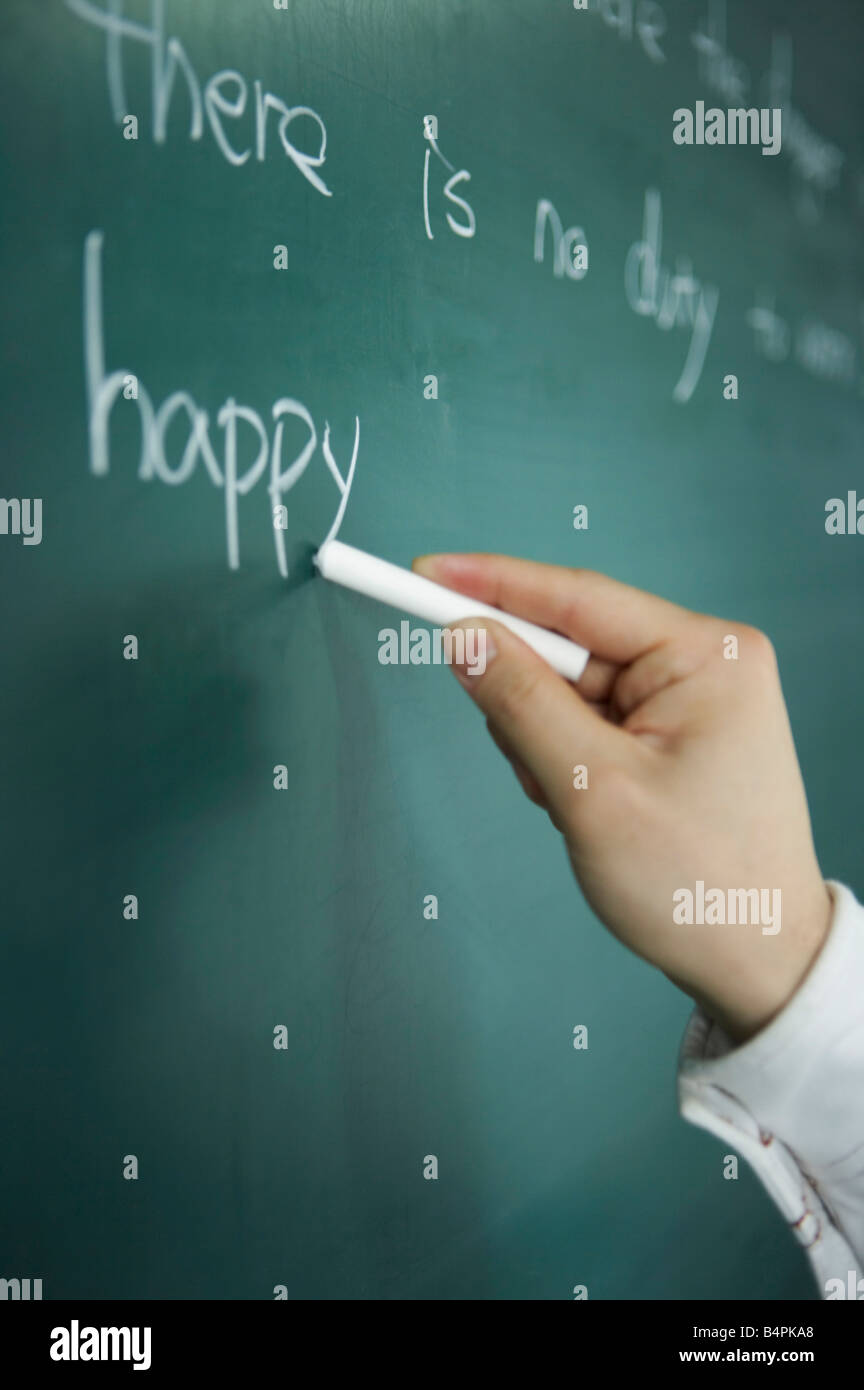 Person writing on blackboard, close-up - Stock Image