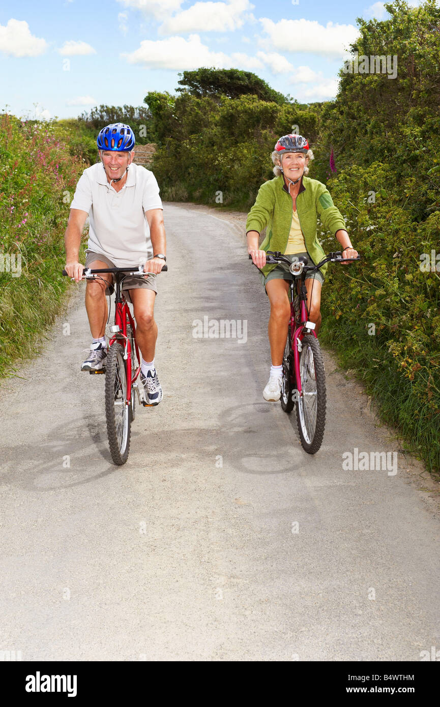 Senior couple cycling on country lane - Stock Image