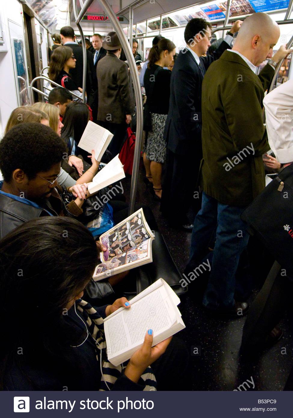 Passengers reading  on New York Subway train - Stock Image