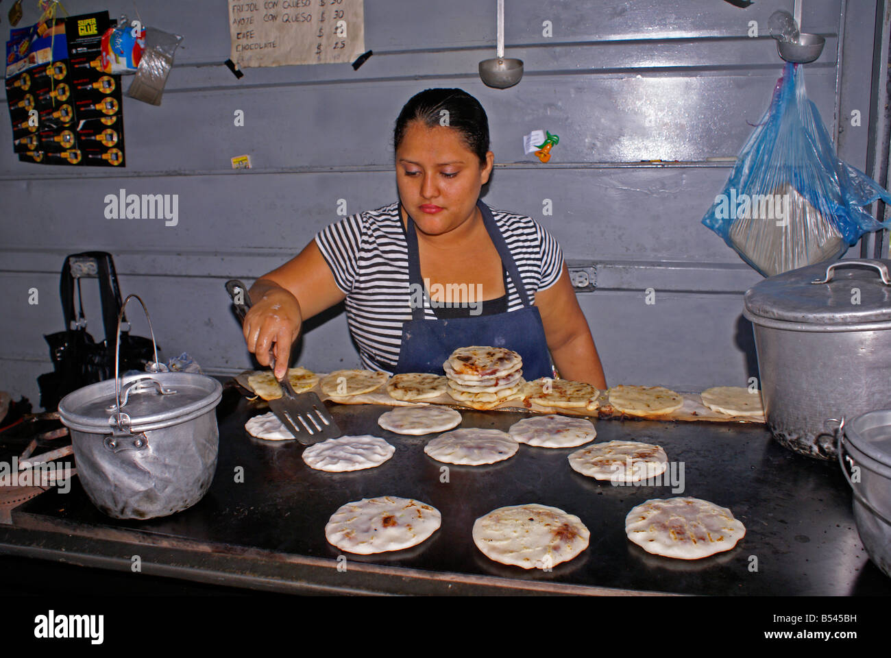 Woman cooking pupusas in a pupuseria, San Salvador, El Salvador Stock Photo
