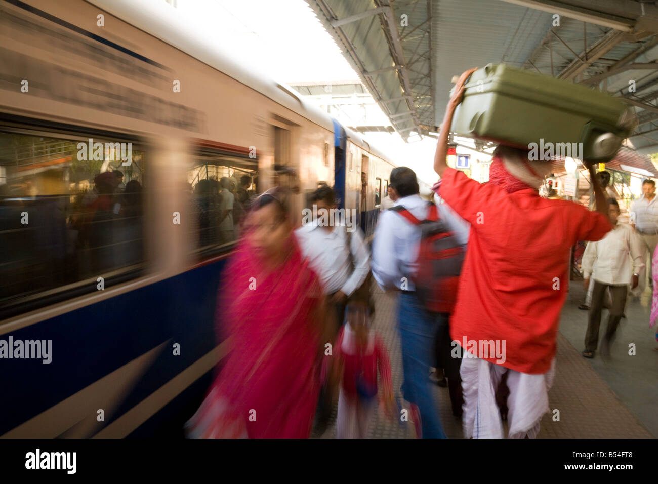 a-porter-carries-bags-as-the-train-comes-into-the-station-india-sawai-B54FT8.jpg