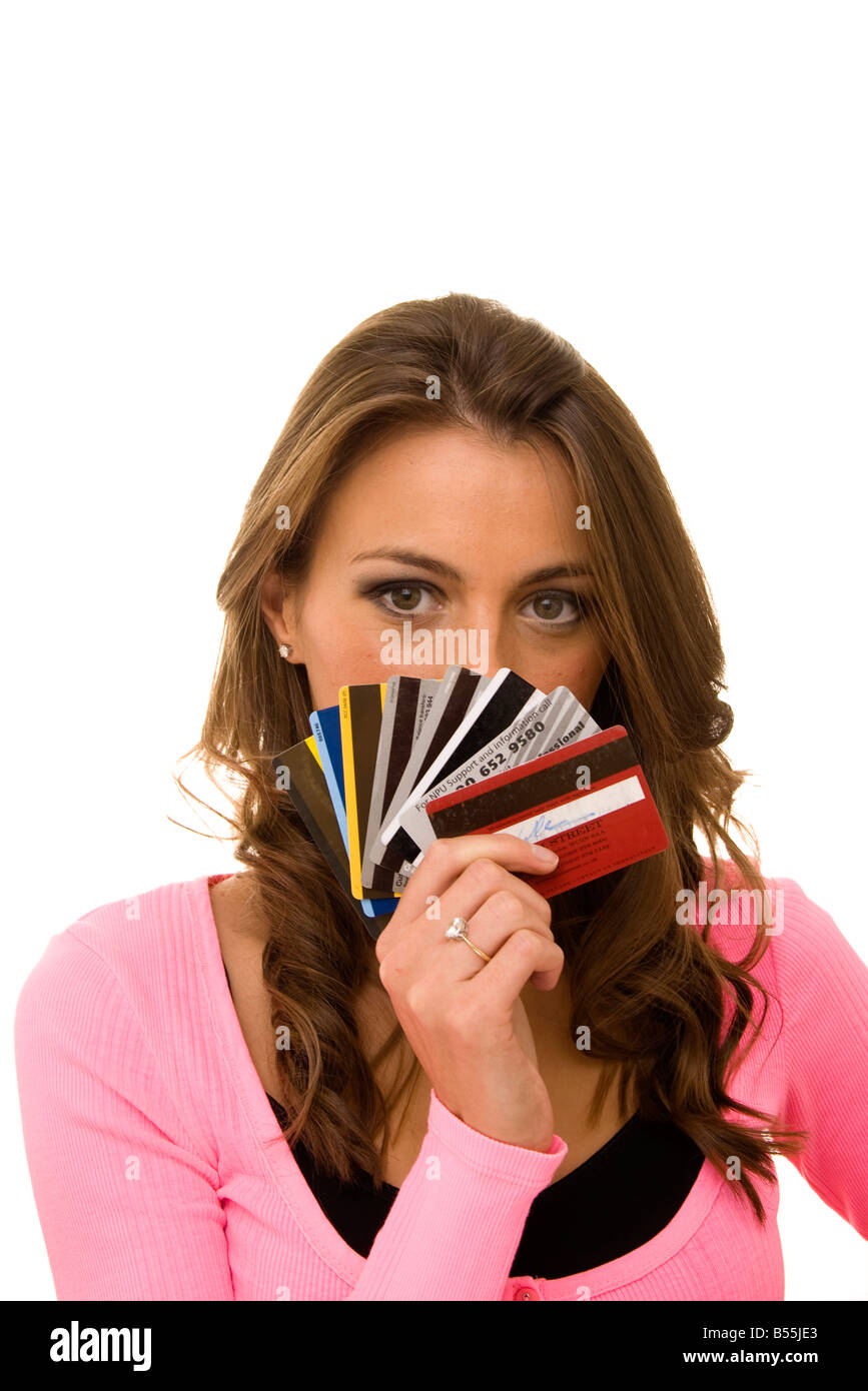 woman holding a bunch of credit cards in front of her face - Stock Image