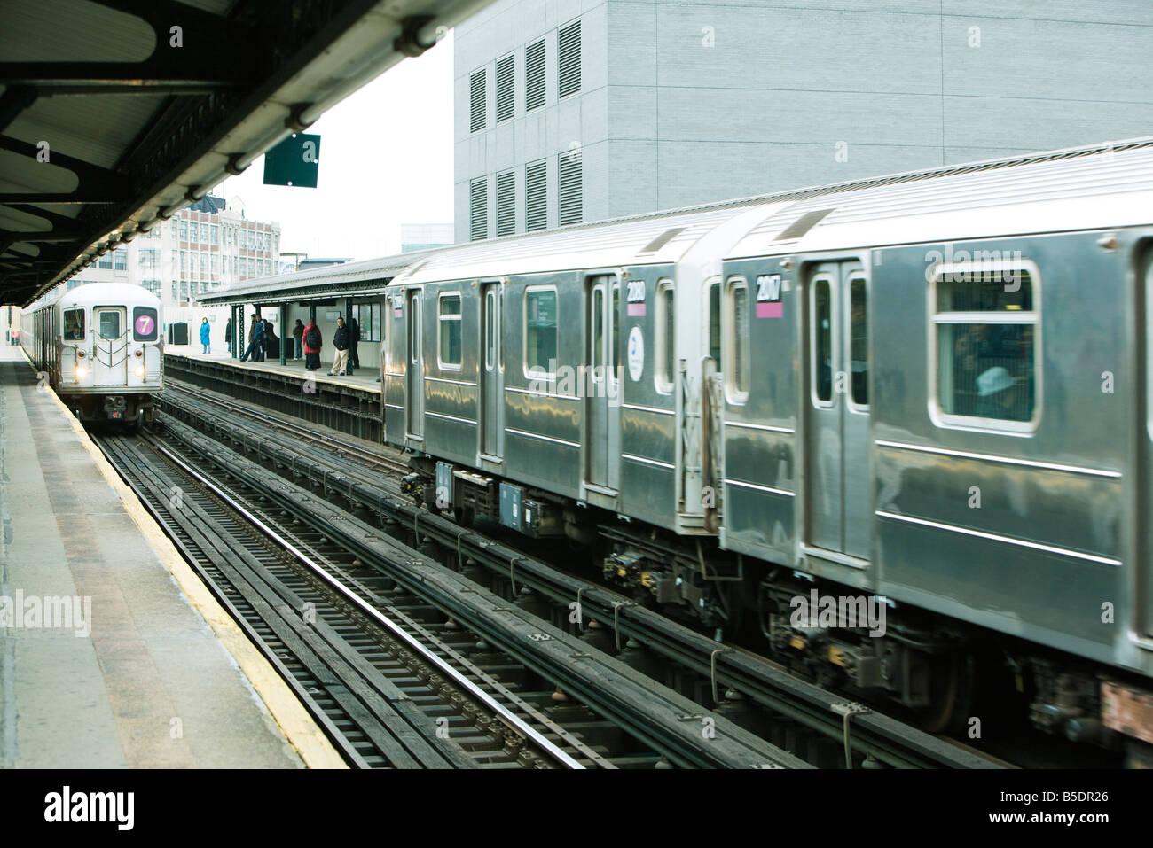Commuters waiting for subway on elevated train platform, IRT Flushing Line of New York City Subway - Stock Image