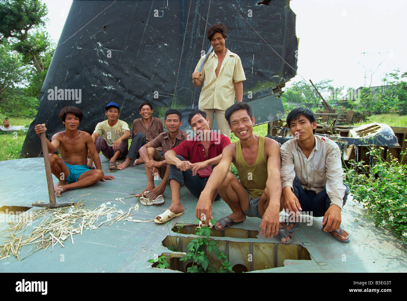 A group of smiling park workers on the tail plane of a crashed US B-52 bomber at Lenin Park, Vietnam, Indochina - Stock Image