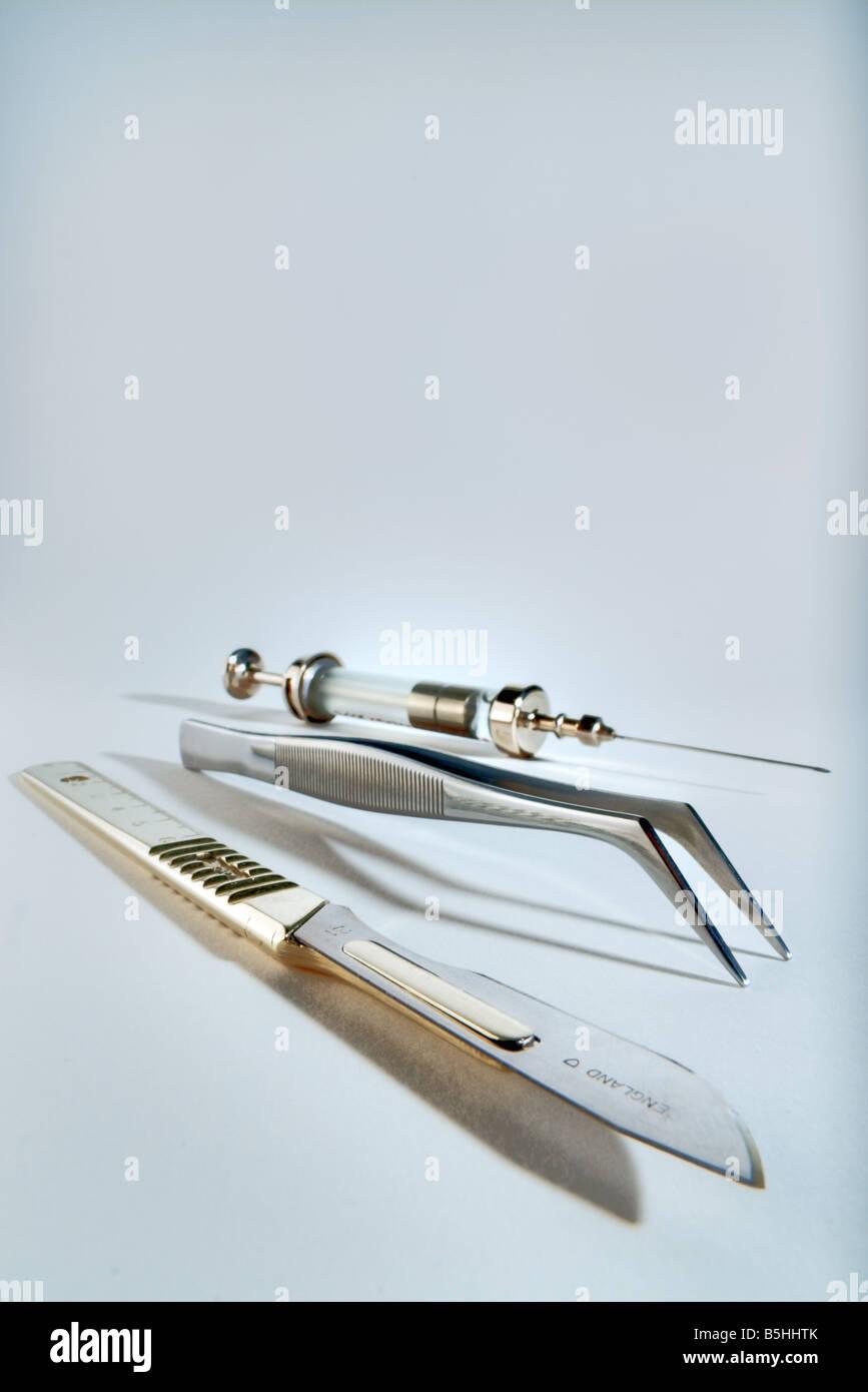 Scalpel, tweezers and a syringe Stock Photo