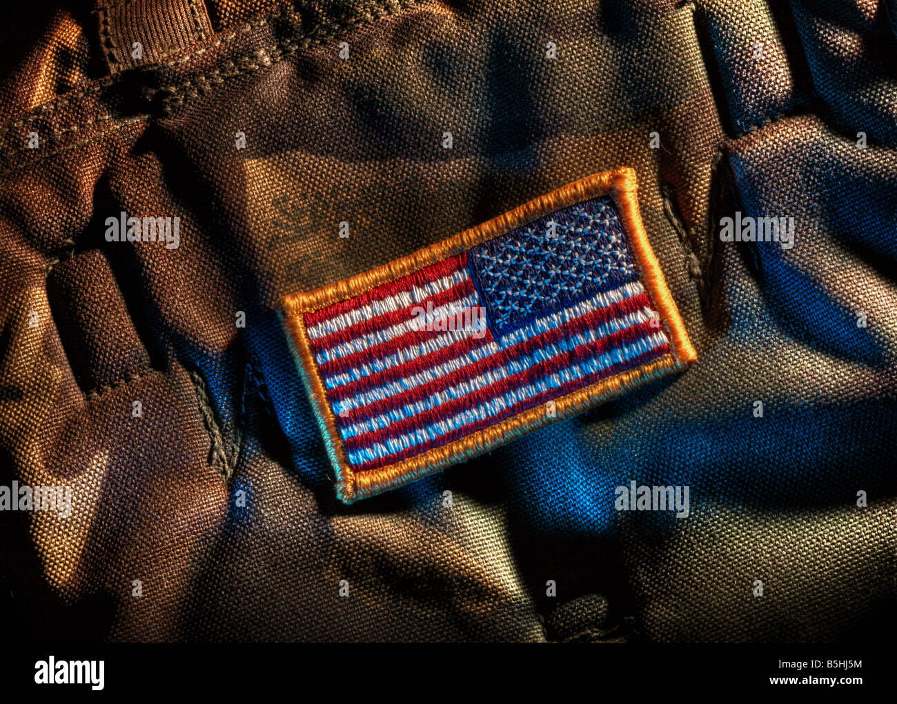 Detachable US flag patch on military camouflage fabric. Mirrored flag is for right shoulder. Stock Photo