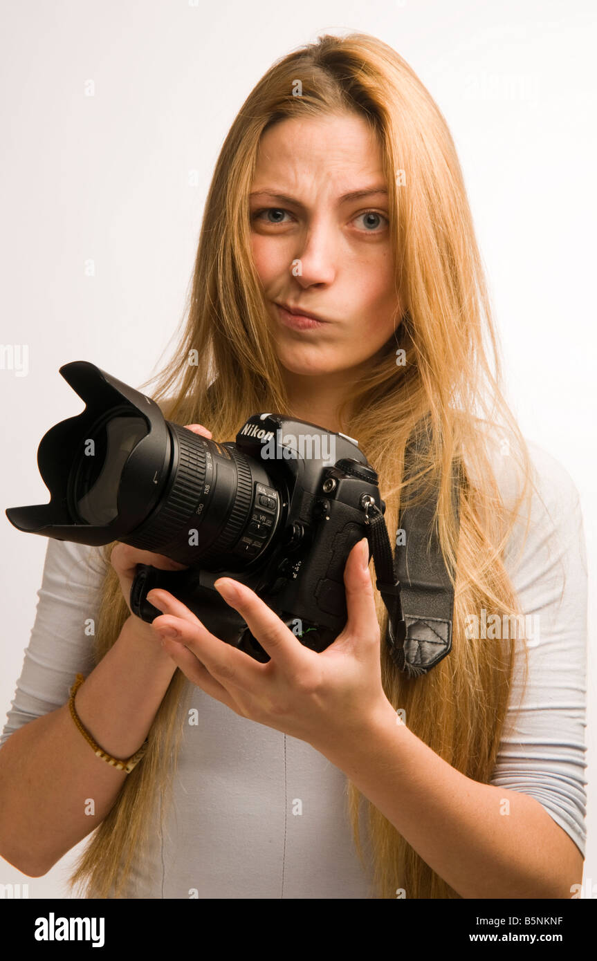 Young woman photographer with expensive Nikon DSLR digital camera unsure of how to use it to take photographs, UK - Stock Image