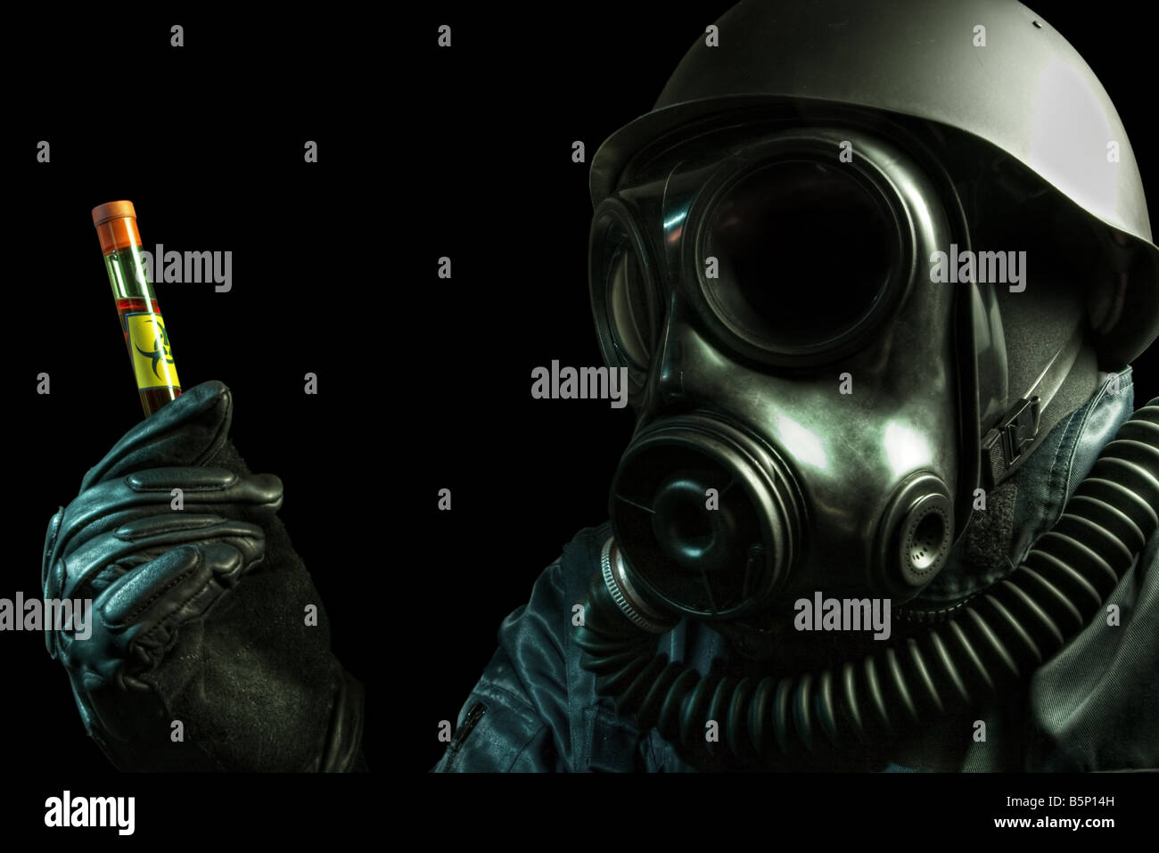 Gas masked man holding a test tube with biohazard symbol Stock Photo