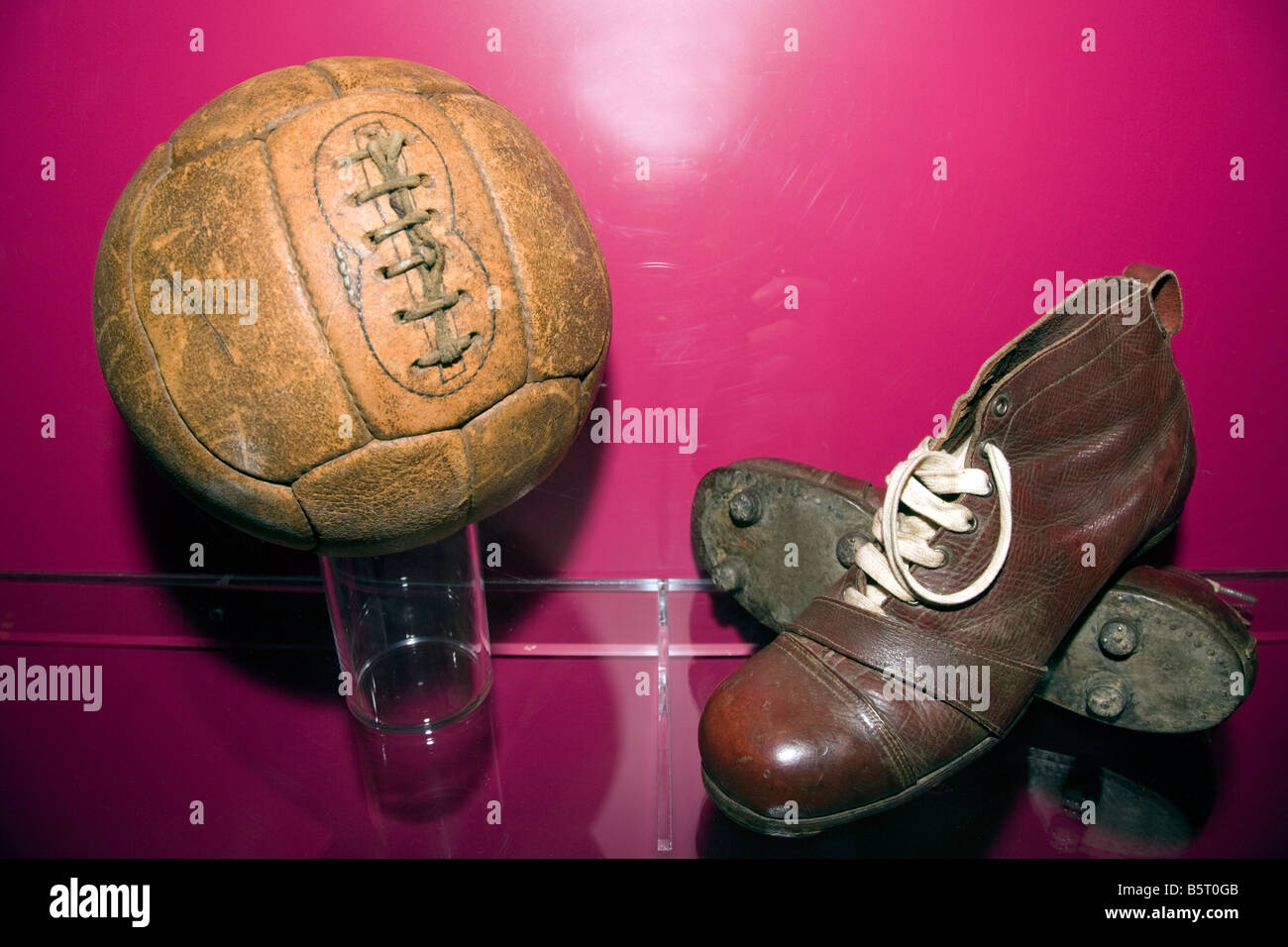 747949574 An old pair of football boots antique leather soles and studs with an old leather  football at Nou Camp