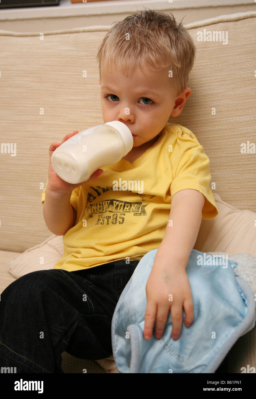 Tired 2 year old boy drinking warm milk from the bottle and holding his  comfort blanket