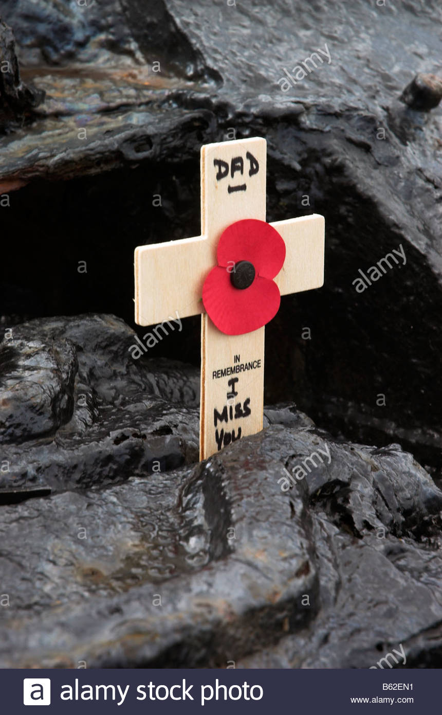 a-wooden-cross-and-red-poppy-dedicated-to-dad-in-the-tracks-of-a-tank-B62EN1.jpg