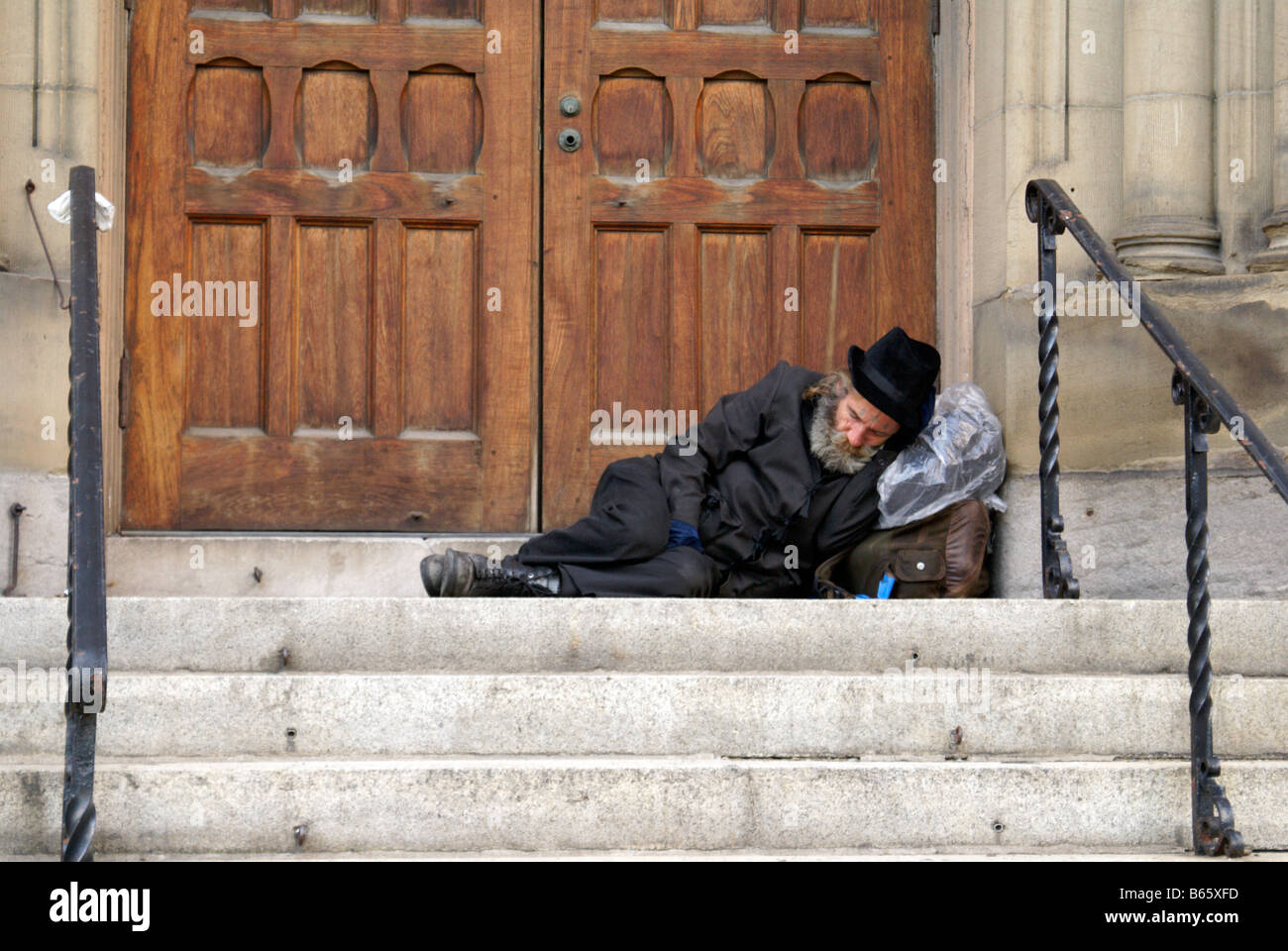 elderly-homeless-man-sleeping-in-a-doorw