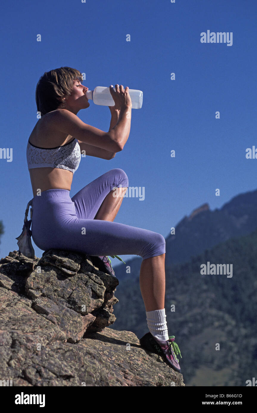 Woman rock climber drinking during a rest break - Stock Image