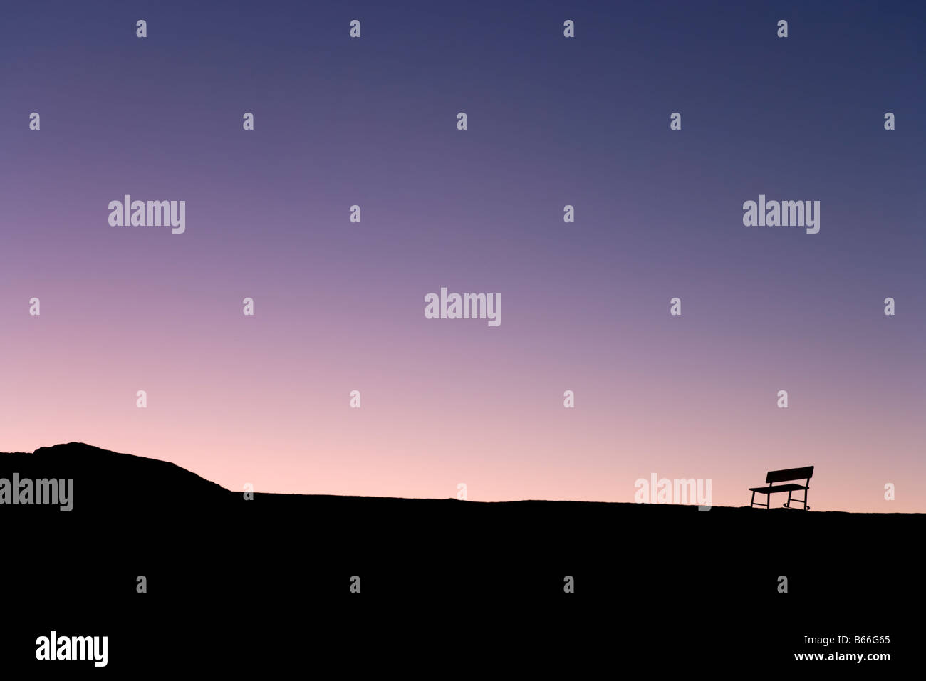 Silhouette of lone bench on the skyline at sunset, Zabriskie Point, Death Valley National Park, California, USA - Stock Image