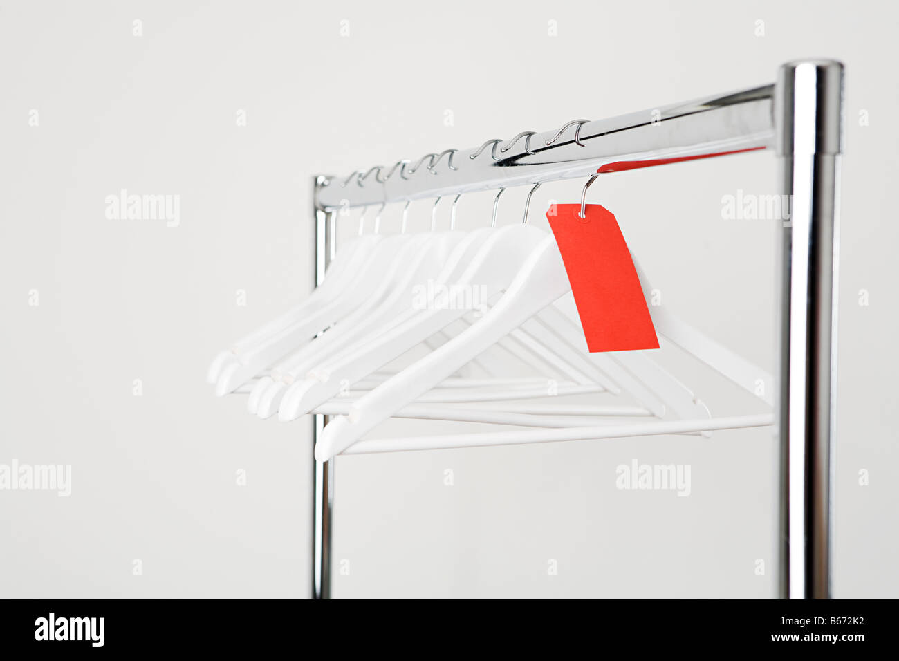 Empty clothes hangers on a rail - Stock Image