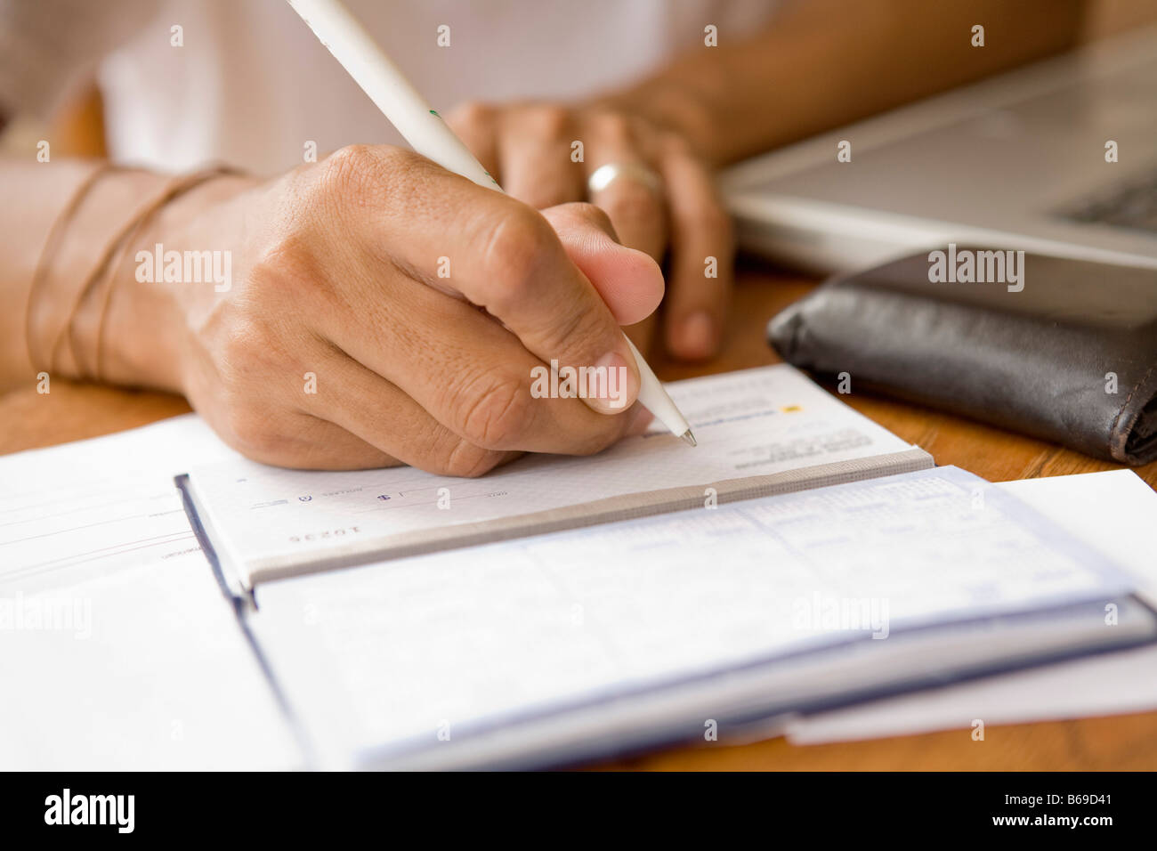 Man signing a check and preparing home finance budget - Stock Image