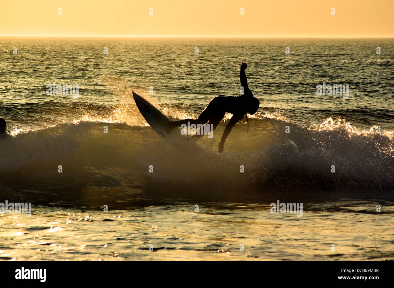 a-surfer-in-action-on-a-wave-at-sunset-a