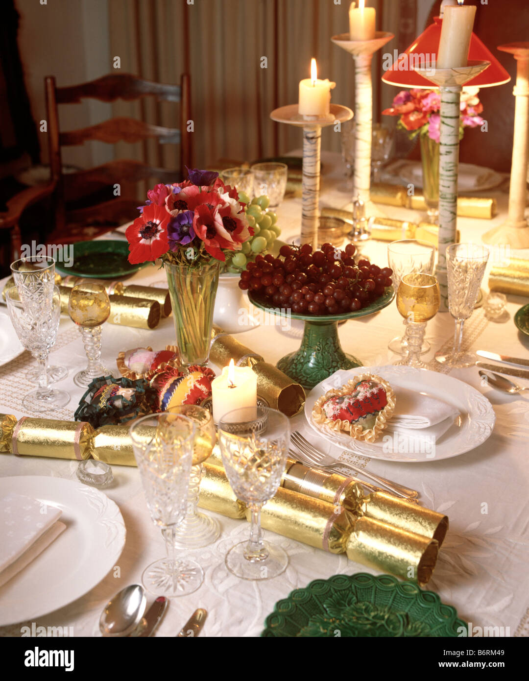 Close-up of table set for Christmas dinner with gold crackers and lighted candles with crockery and cutlery & Close-up of table set for Christmas dinner with gold crackers and ...