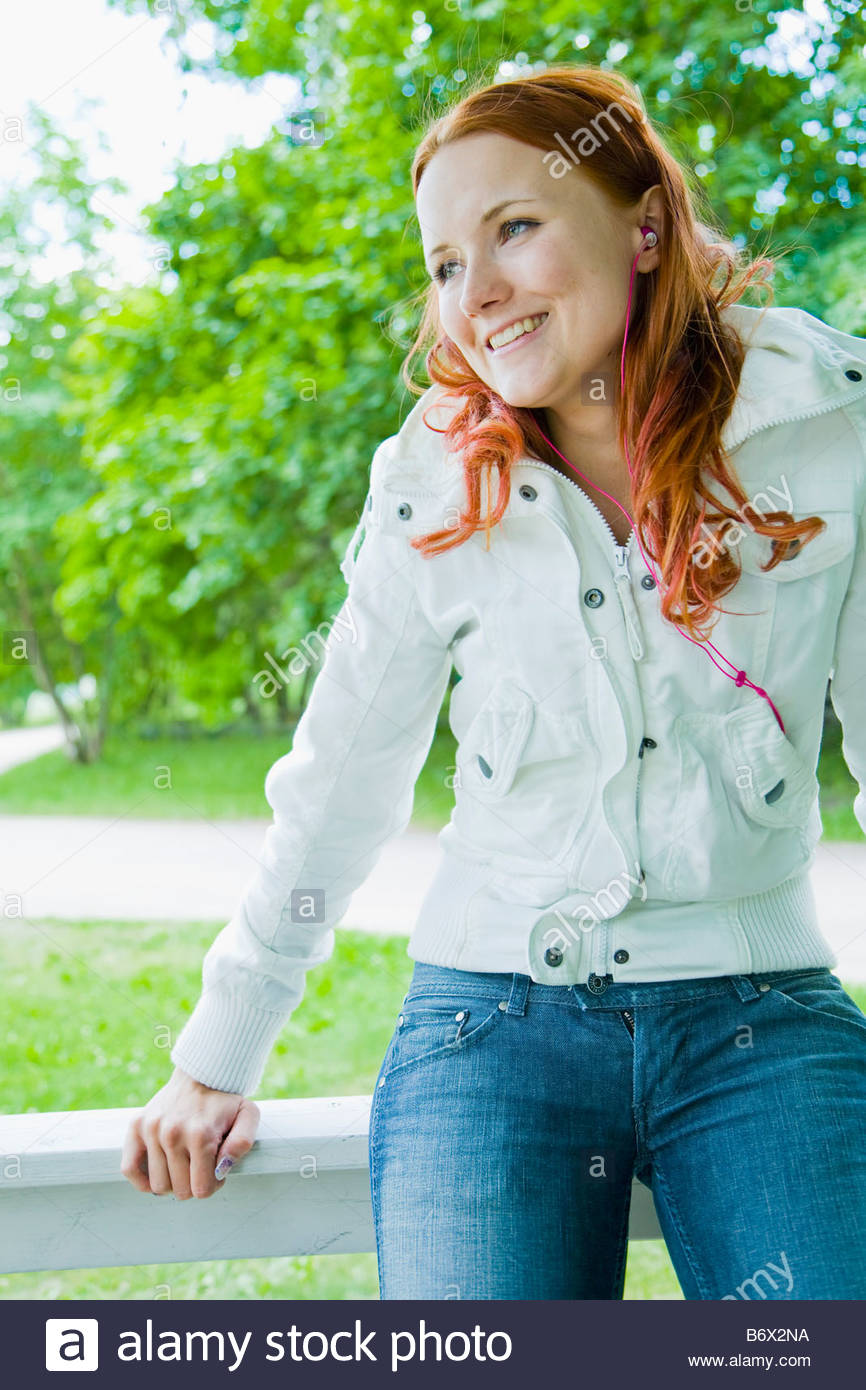 Girl sitting on a rail - Stock Image