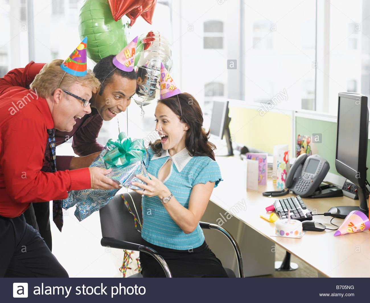 Businessmen Giving Birthday Gift To Co Worker