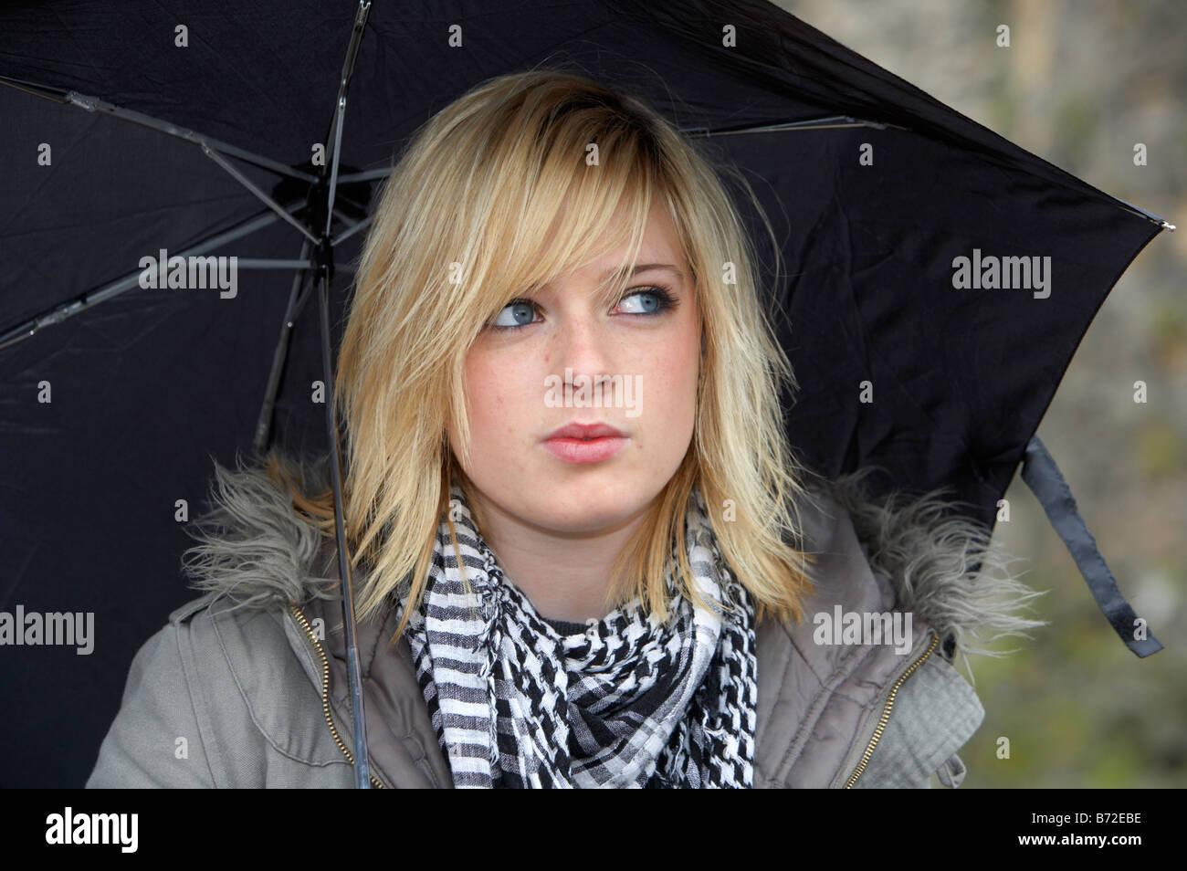 blonde 18 year old girl holding black umbrella wearing jacket and