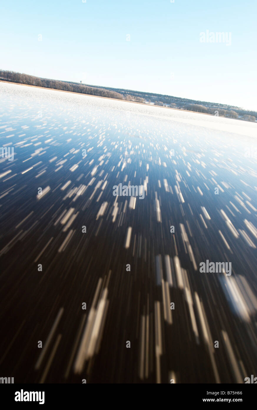 Ice skating on frozen lake, motion blurred ice surface - Stock Image
