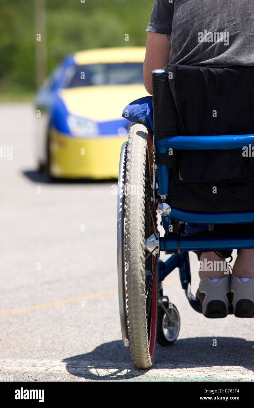 Person on wheelchair facing racing car, rear view - Stock Image